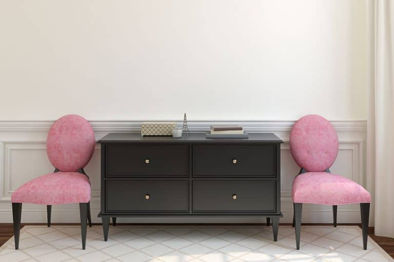 A black dresser with two small pink upholstered chairs on each side, What Color Knobs For A Black Dresser? [7 Fabulous Options To Consider]