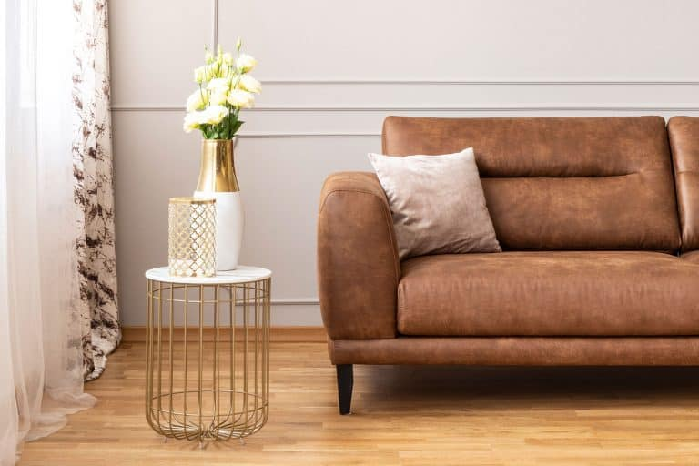 A brown leather sofa with a small accent table on the side decorated with flowers, 10 Locations To Put Flowers In The Living Room