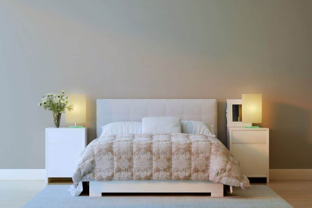 A cream walled bedroom with lamps on the nightstand