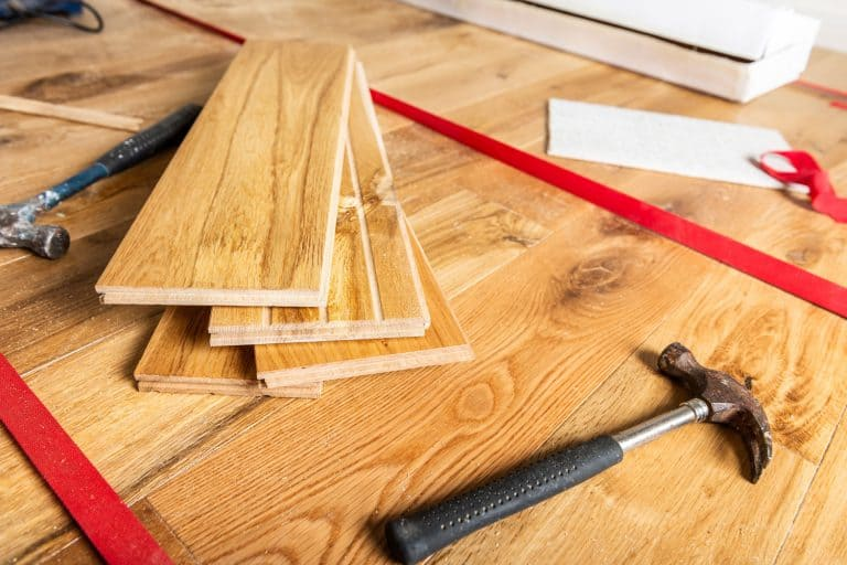 A floorboard being installed in the living room, How To Fix A Cracked Floorboard