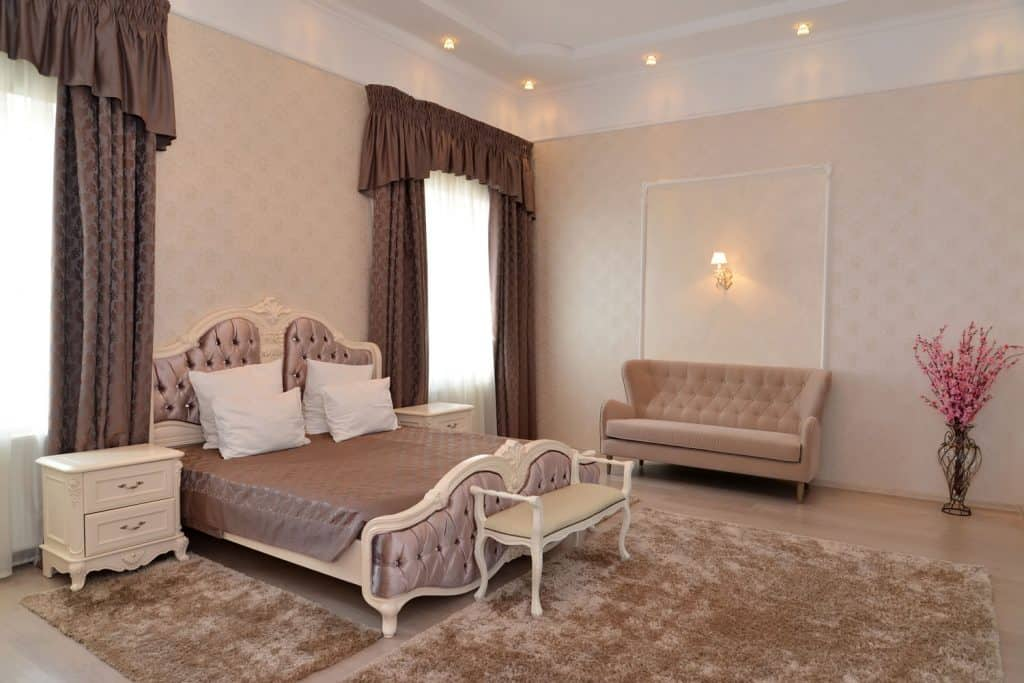 A gorgeous beige colored bedroom with brown curtains, carpeted flooring, and recessed lighting