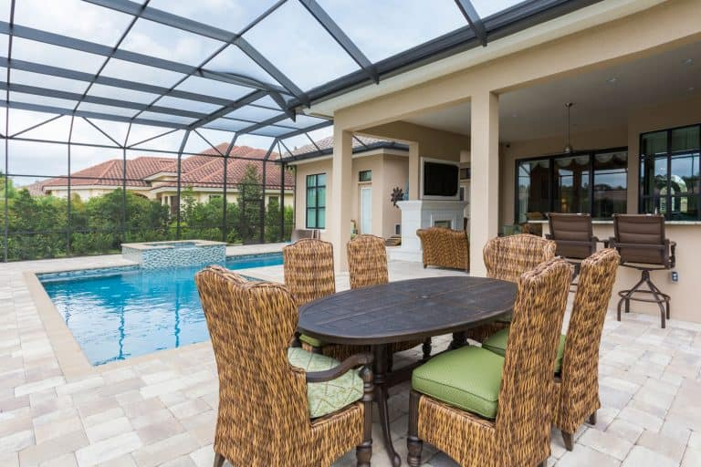 A gorgeous lanai screen on the back of a contemporary house patio with a pool on the back, How Much Does It Cost To Build A Lanai In Florida?
