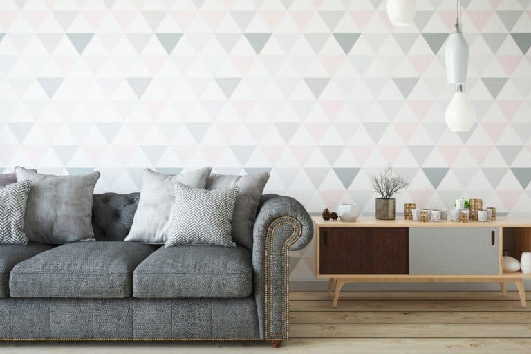A gorgeous living room with a gray couch and gray throw pillows with a patterned wallpaper background, A gorgeous living room with a gray couch and gray throw pillows with a patterned wallpaper background