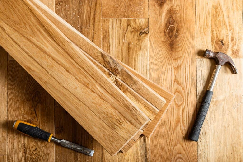 A hammer and thief and chisel used for installing a wooden flooring