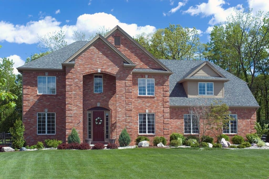 A huge red brick mansion with a gorgeous newly lawn landscaping