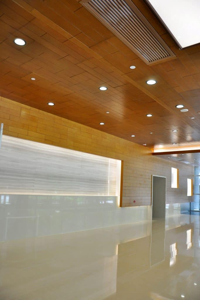 A contemporary hallway with wooden recessed lighting and tiled flooring