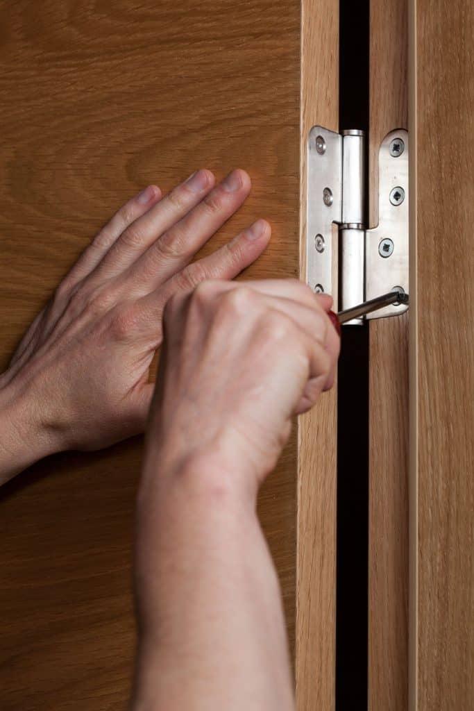 A man screwing the bedroom door hinges tightly