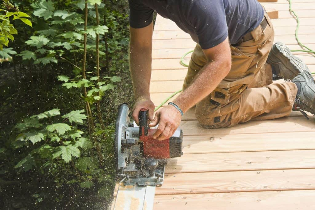 A man using a plunge saw to trim the edge of the boardwalk