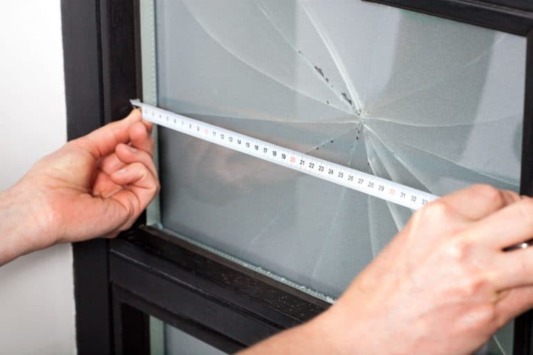 A professional measuring the window with a huge crack in it, How To Fix A Cracked Window On Your House