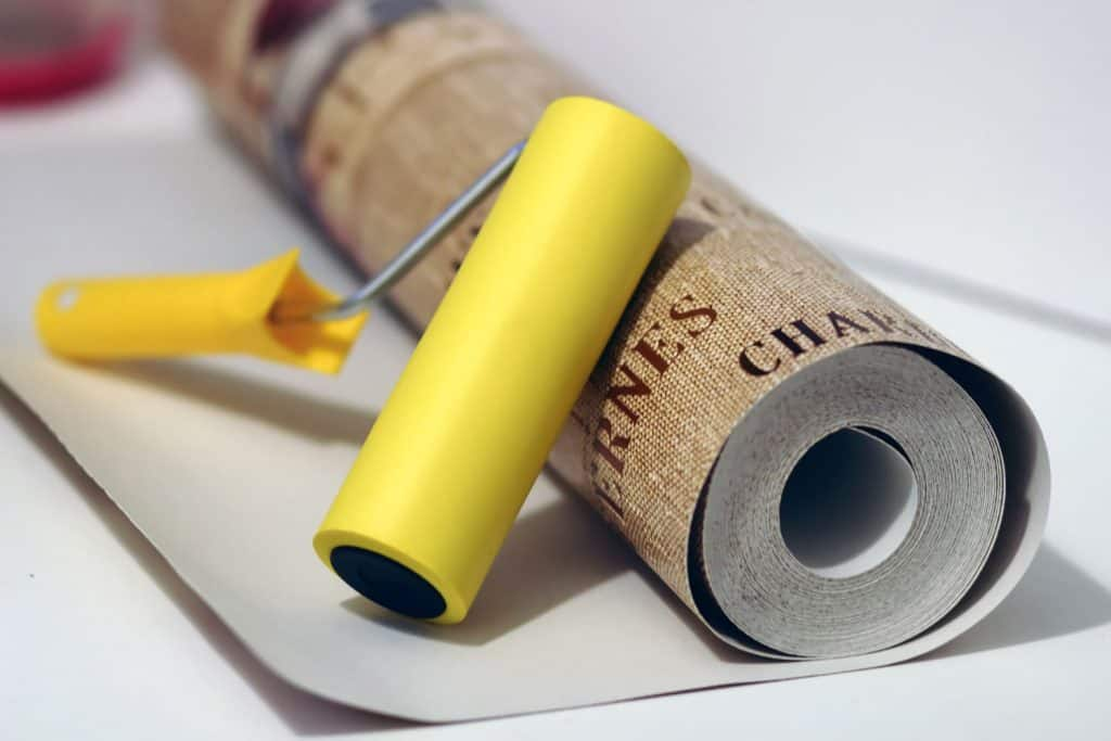 A rolled wallpaper with a yellow roller for the glue