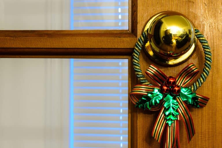 A small Christmas decoration hanged on t he golden door knob of an office, How To Decorate Your Office Door For Christmas