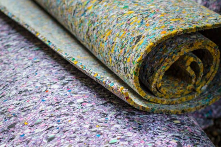 A thick carpet padding rolled and stored, How Thick Should Carpet Padding Be?