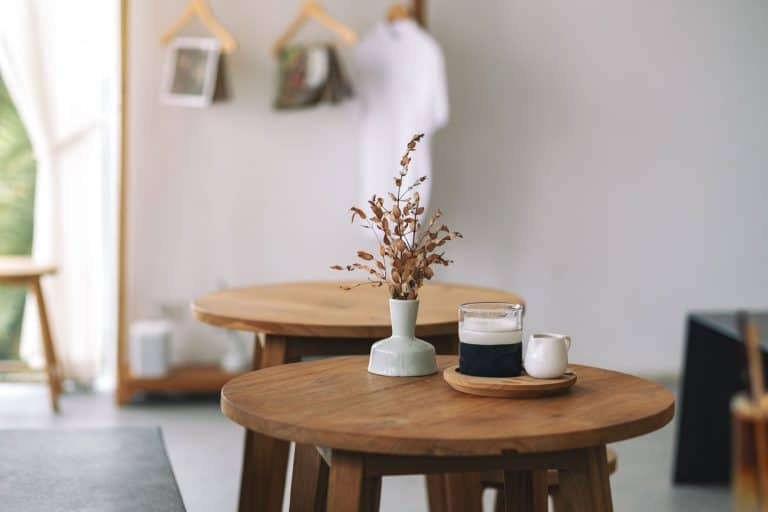 A wooden coffee table with a small vase with small flowers, How To Style A Round Coffee Table