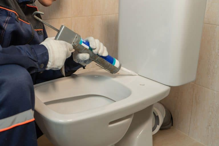 A worker caulking the toilet tank, How To Fix A Cracked Toilet Tank, Bowl, Or Base [A Complete Guide]