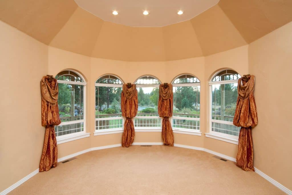 An empty room with a bay window painted in beige, brown curtains, and recessed lighting