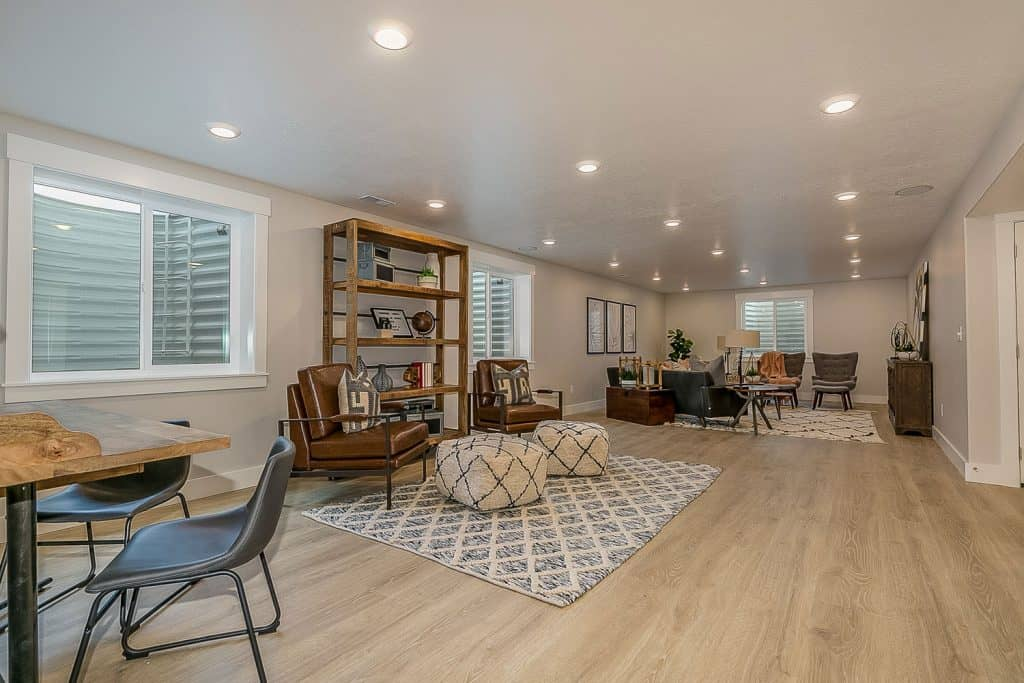 An open space living room and kitchen with laminated flooring, recessed lighting, and mid century modern furnitures
