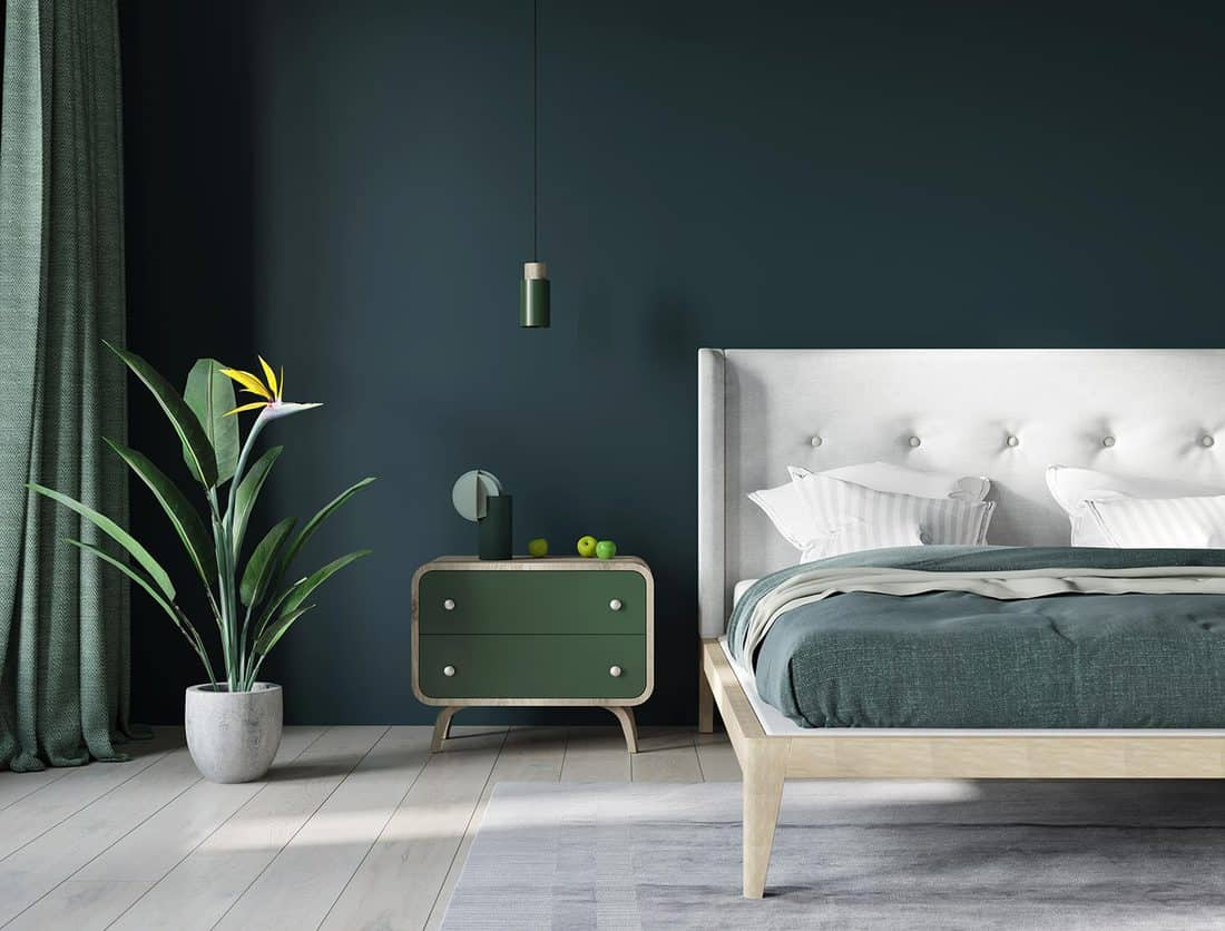 Bedroom near window in dark green and light beige