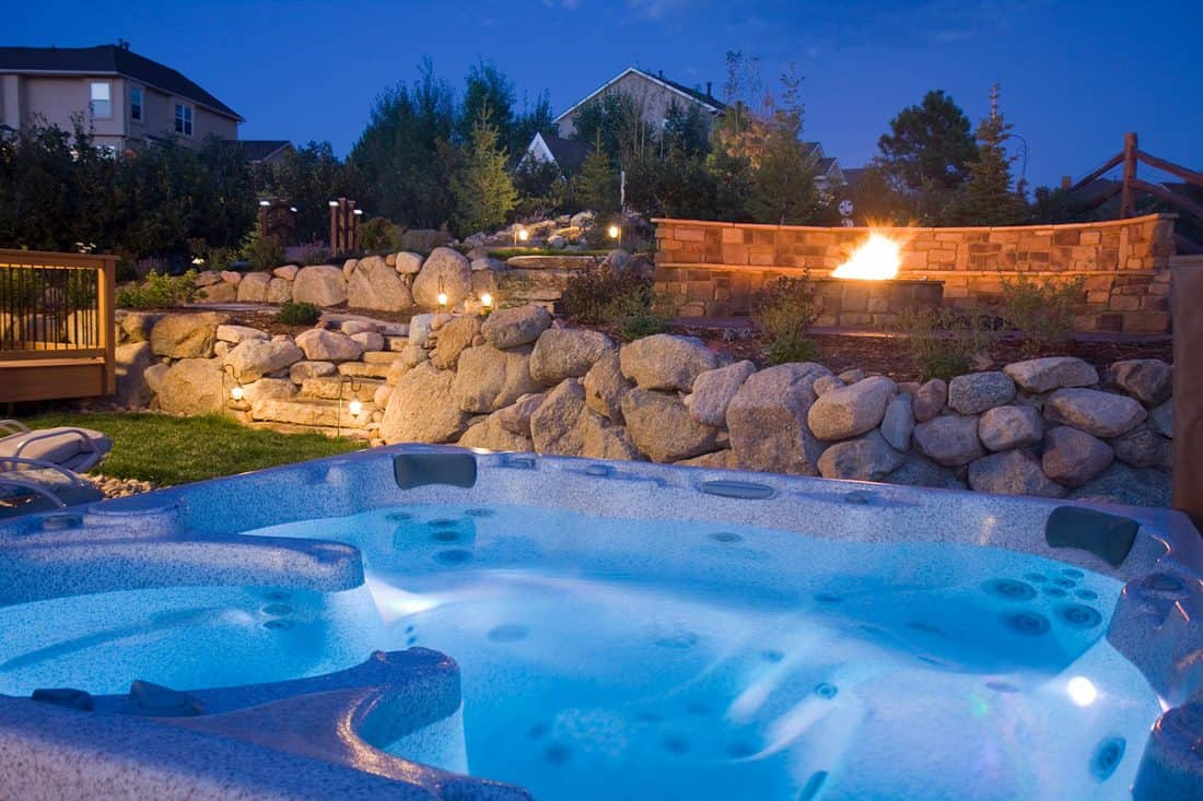 Brilliant Blue hot tub in the foreground and awesome fire pit and landscaping in the background