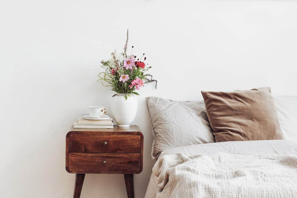 Cup of coffee and books on retro wooden bedside table. Rustic white ceramic vase with bouquet of pink cocmos and zinnia flowers. Beige linen and velvet pillows in bed, Scandinavian interior, bedroom.