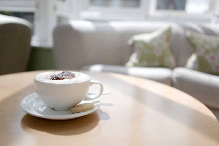 Cappuccino in a cup on a coffee table, How To Turn A Kitchen Table Into A Coffee Table