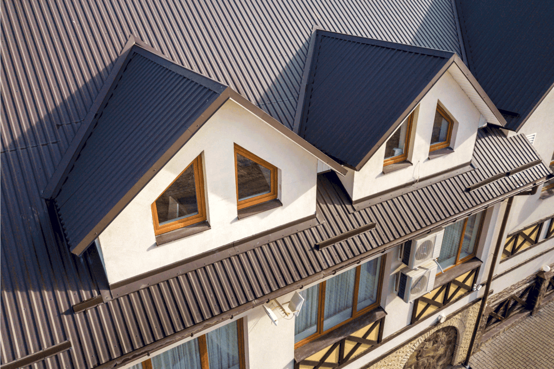 Close-up aerial view of building attic rooms exterior on brown metal shingle roof, stucco walls and plastic windows.