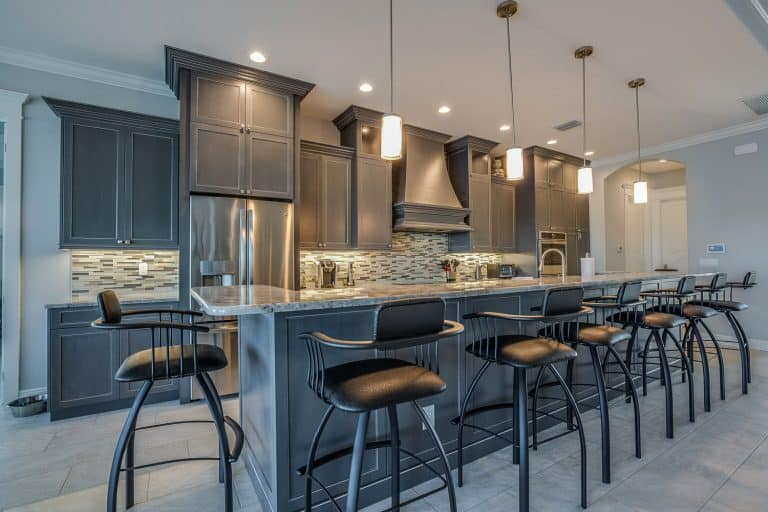 Dark gray cabinets and pendant lights adorn this classy kitchen with bar stools, How Much Space Between Bar Stools?