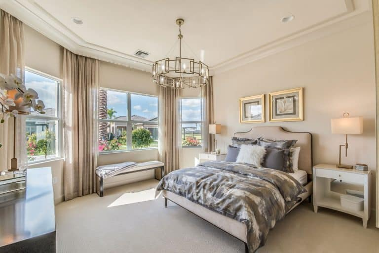 Elegant staged furnishings in master bedroom, How Big Should A Master Suite Be? [Including 11 Great Examples!]
