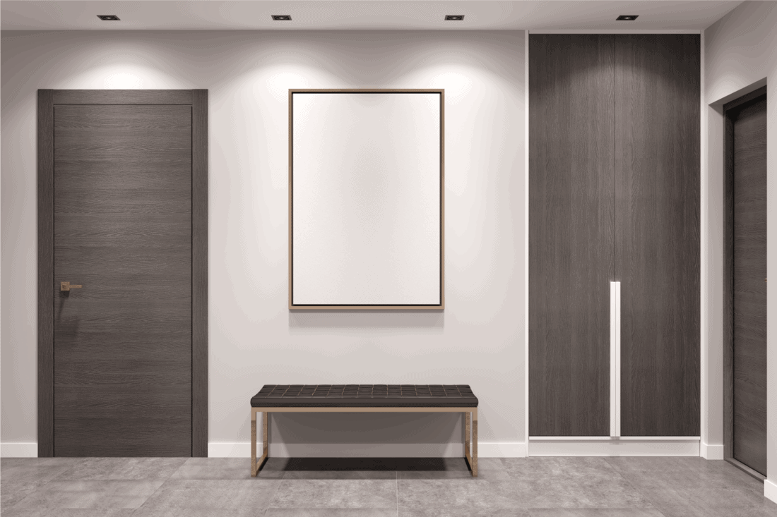Empty gray hallway with closed doors, a dark wooden wardrobe, a bench and a blank mockup poster on the wall