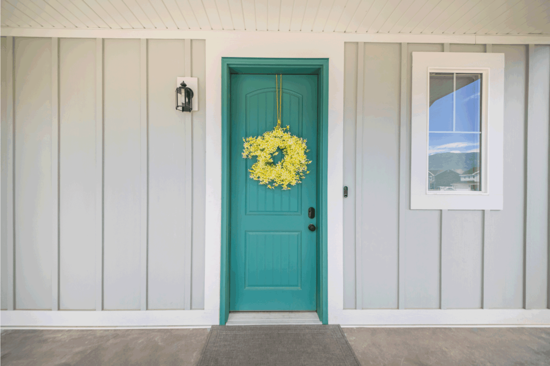 Exterior of the house with gray walls and blue-green doors with yellow floral wreath