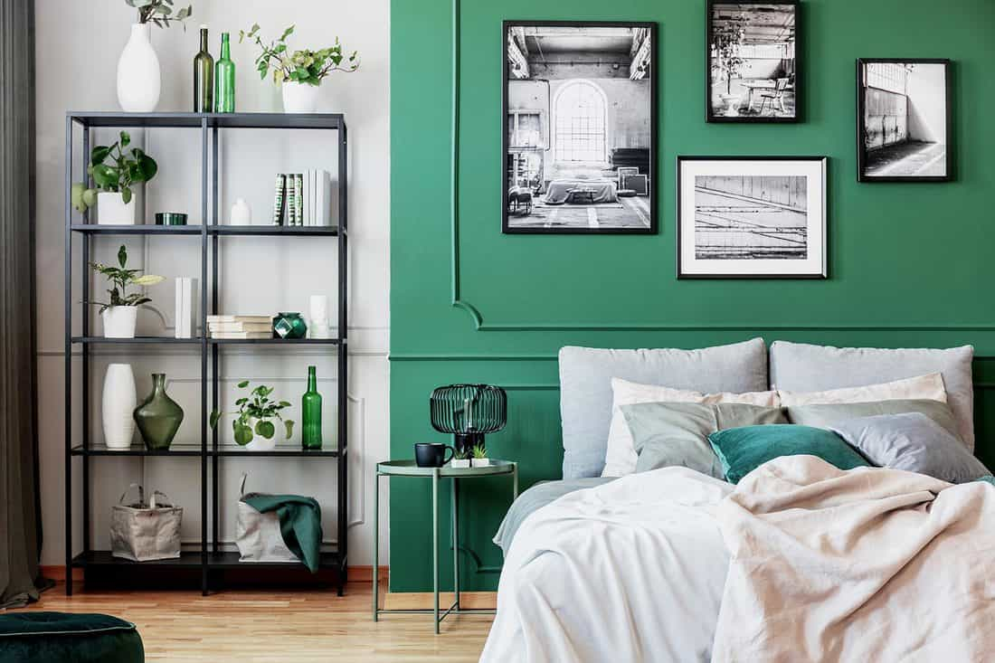 Gallery of black and white poster on green wall behind king size bed with pillows and blanket
