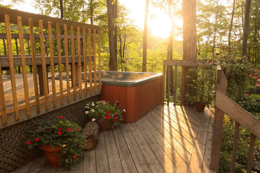Gorgeous landscaped wooden deck with sun shining through trees of surrounding forest into mist of hot tub