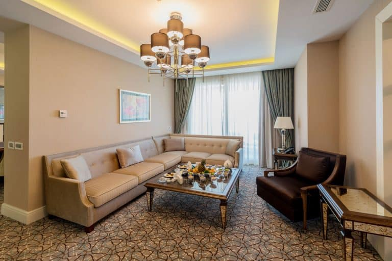 Gorgeous tan living room with a chandelier on the center and carpeted flooring with cream furnitures, What Color Walls Go With Cream Or Tan Trim?