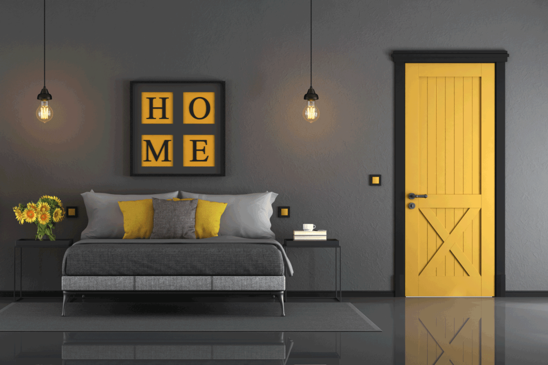 Gray and yellow master bedroom with double bed, closed door and mannequin