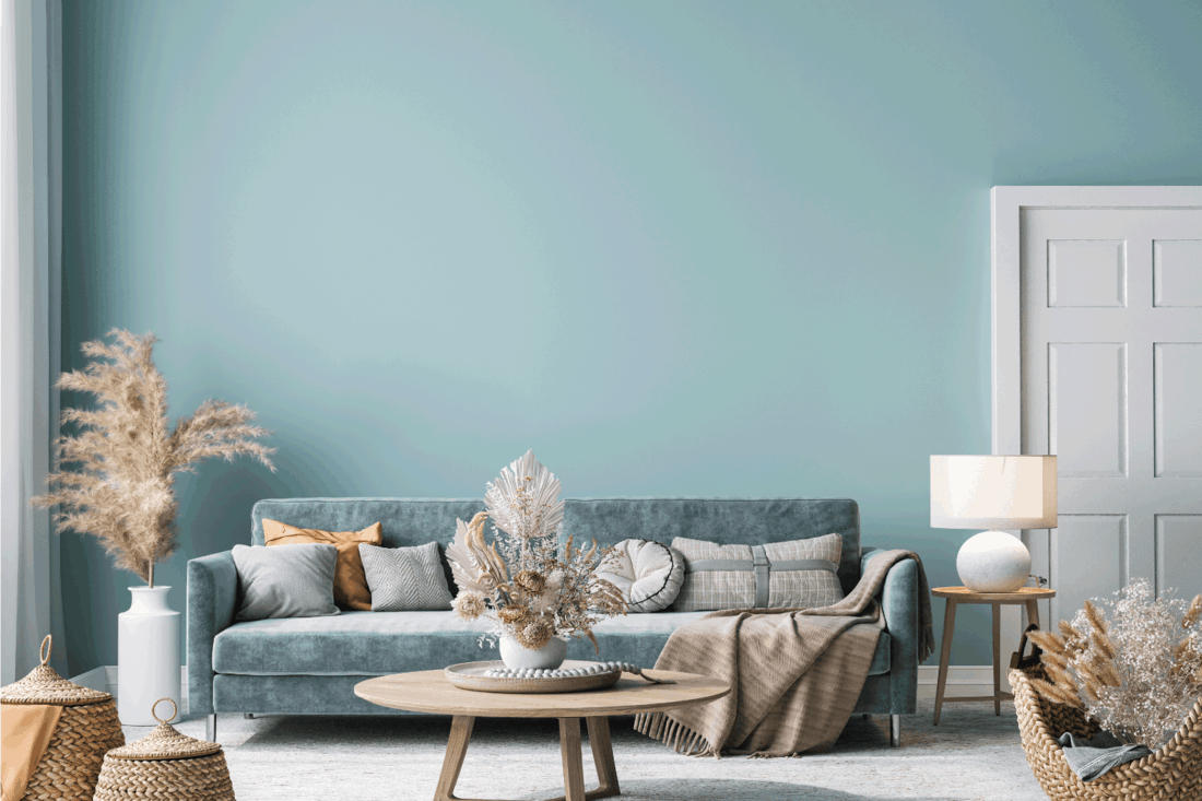Home interior with blue sofa, wooden table and decor in blue living room