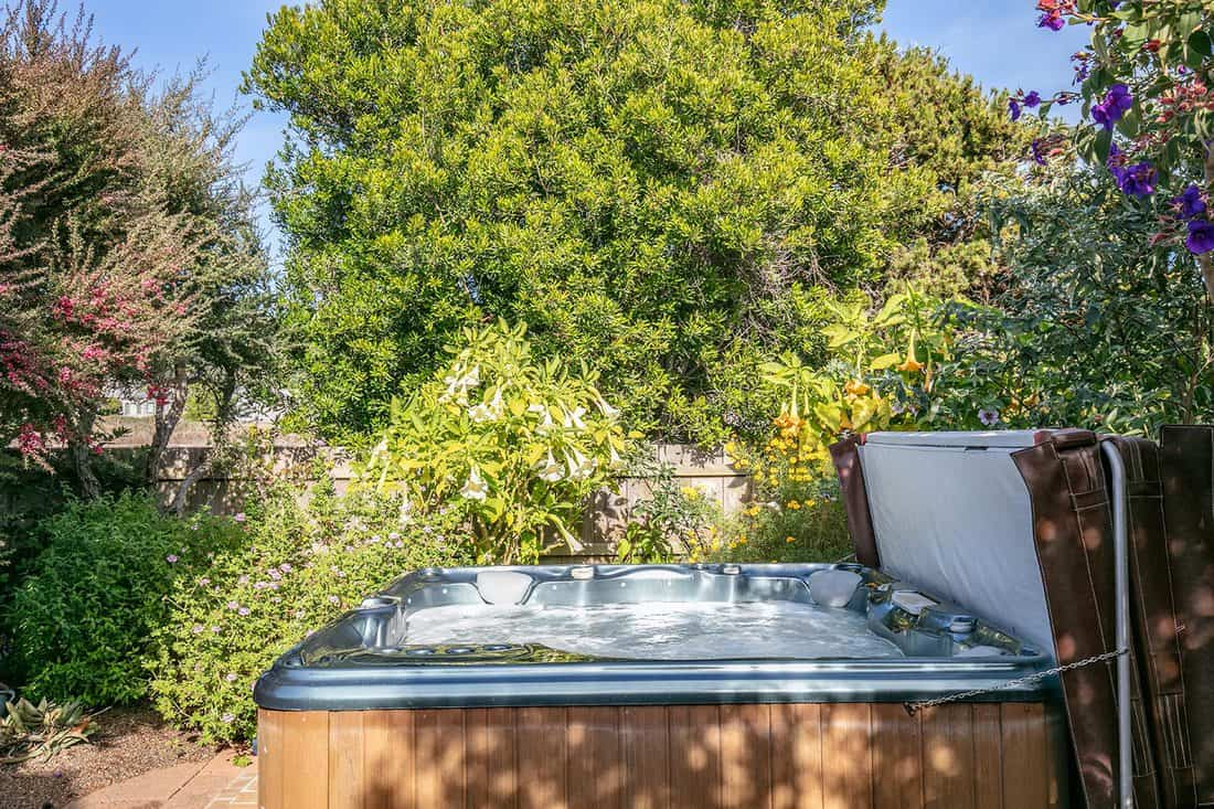 Hot tub in garden of home during the day with no people
