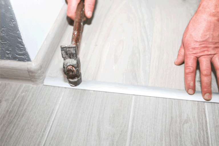 Installation-of-threshold-indoors.-Renovation-works-in-the-flat.-Man-with-a-hammer.How-To-Make-Tile-Flush-With-Hardwood-Floor