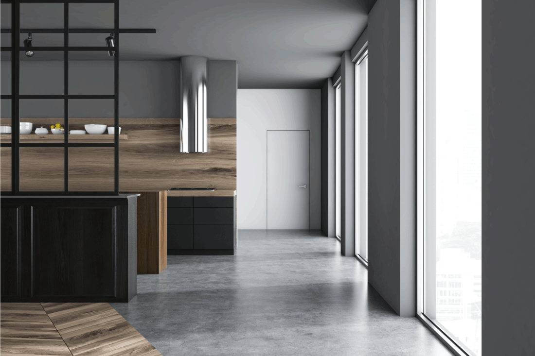 Luxurious interior kitchen gray walls, concrete flooring, black boards and white doors