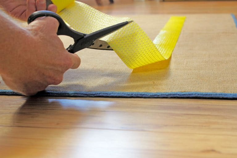 Male caucasian hands with black handle stainless steel scissors cutting to size a strip of yellow anti-slip rug grip tape. Cutting and placing anti-skid carpet tape, How To Stop Plastic Carpet Protector From Moving