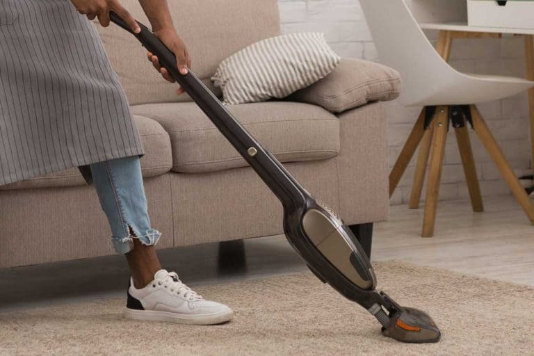 Man cleaning house with wireless vacuum cleaner, How Long Does A Bissell Carpet Cleaner Last?