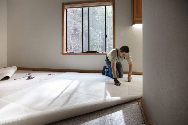 Man installing carpeting in home, Does Carpet Installation Include Moving Furniture?
