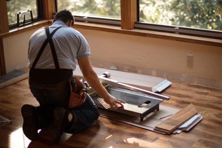Man installing wood flooring in home, How To Cut Hardwood Floors Near A Wall
