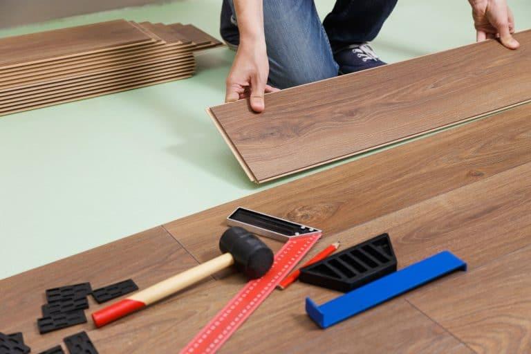 Man installing laminate hardwood floor planks in new house, How Wide Are Hardwood Floor Planks?