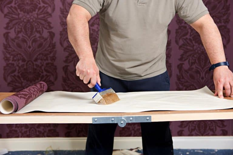 Man putting glue on wall paper on the preparation table, Does Wallpaper Paste Glue Dry Clear?
