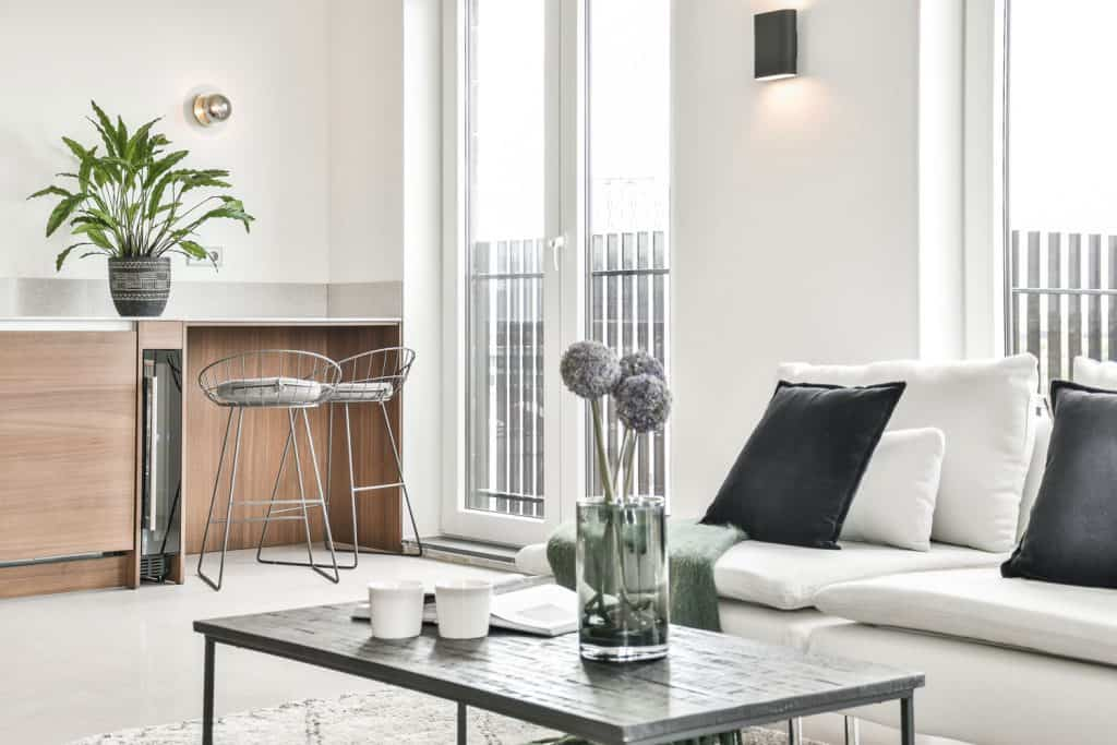Minimalist themed white living room with cozy furniture's and a gray minimalist coffee table