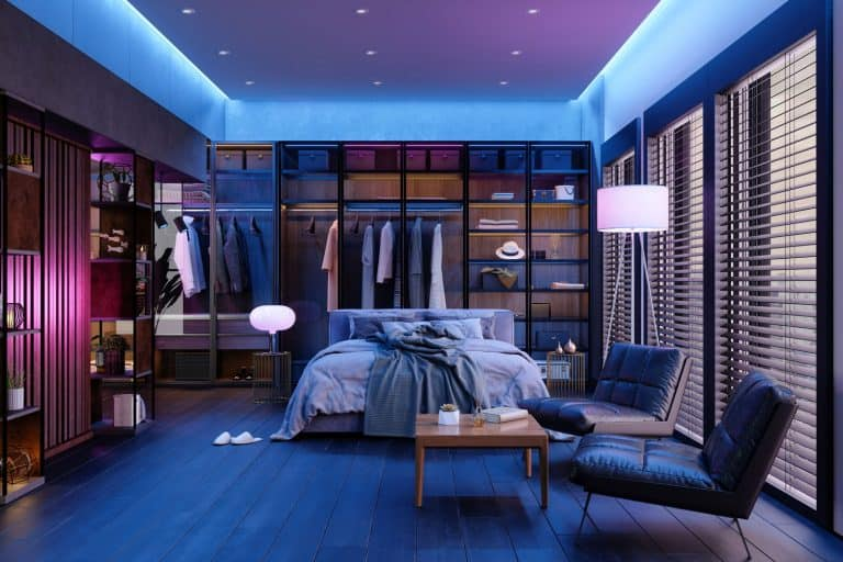 Modern Bedroom Interior At Night With Neon Light. Messy Bed, Clothes In Closet, Armchairs And Floor Lamp, Why Does My Bedroom Get So Hot At Night? [And What To Do About It]