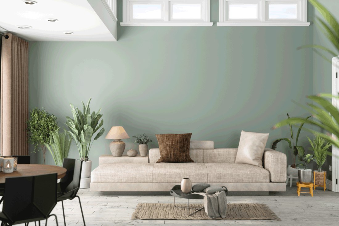 Modern Living Room Interior With Green Plants, Sofa And Green Wall Background