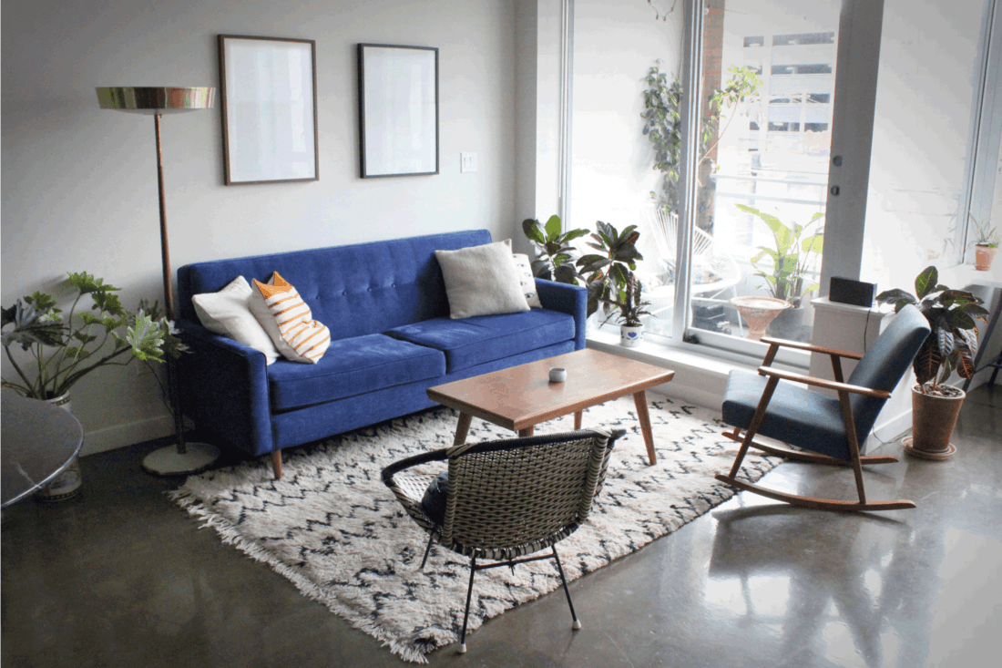 Modern apartment with concrete floors furnished with mid century modern furnishings and minimalist interior design