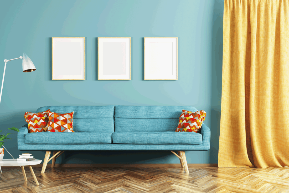 Modern interior design of living room with blue sofa, coffee table, frames and window