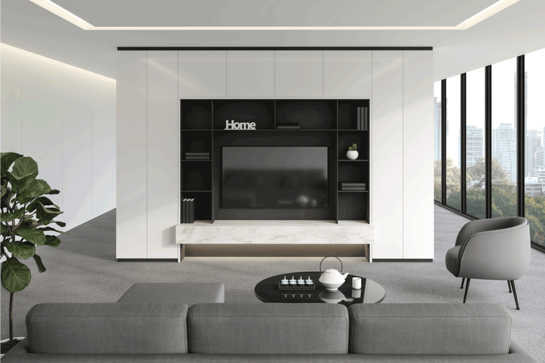 Modern living room with minimalist TV background, gray carpet flooring and white painted walls, gray furniture with large windows overlooking the city