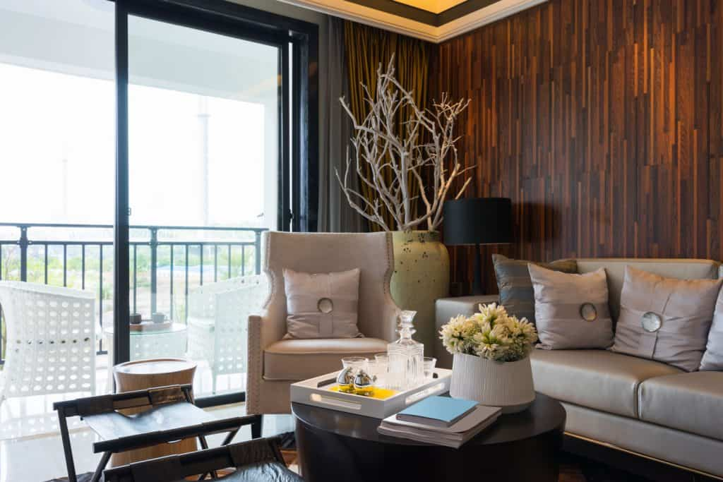 Modern luxurious living room with beige sofas, decorative withered trees and a coffee table with whiskey